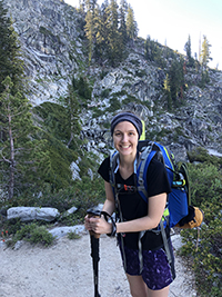 A woman smiling while on a hike.