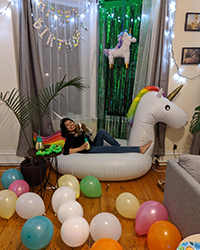 A woman posing on a blow-up unicorn at her birthday party with balloons all over the ground.