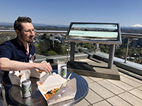 A man eating lunch outside on a sunny day at a table on balcony at OHSU, with Mt. Hood visible in the background.