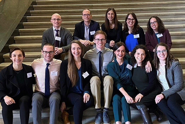 A group of OHSU Pediatric Residents sitting together on stairs at the Oregon State House.