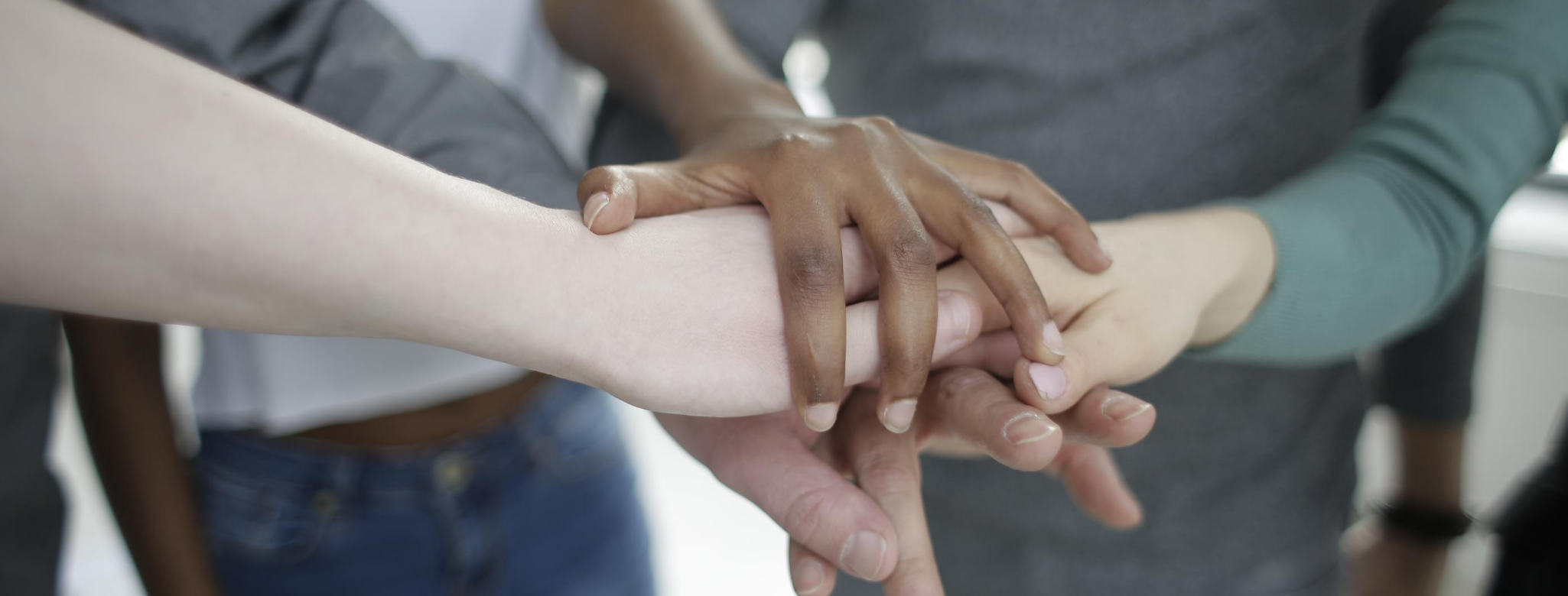 Image of multi-racial hands stacked up in cooperative manner.