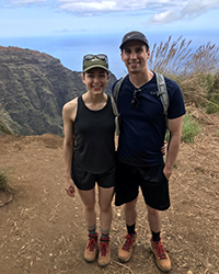 A woman and a man smiling while on a hike, with the ocean in the background.