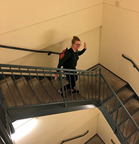 A photo of Kristina Haley waving as she walks down a flight of stairs.