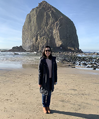 A woman at the beach on a sunny day with a large coastal rock in the background.
