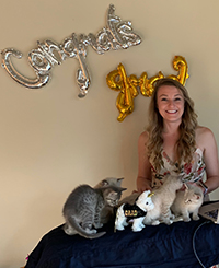 "A woman smiling sitting with several kittens with a sign behind her that reads ""Congrats Jenn."""
