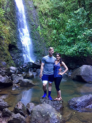 A man with his arm around a woman pose in front of a waterfall while on a hike.