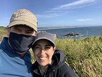 A woman and a man outside smiling with the Oregon coast in the background.