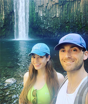 A man and a woman smiling taking a selfie with a waterfall in the background.