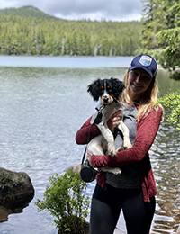 A woman standing in front of a lake holding her dog.