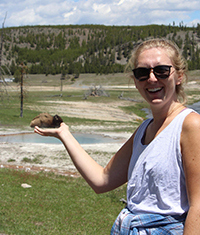 A woman posing with her hand out to give the impression that she is holding a buffalo that is sitting down off in the distant background.