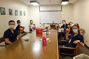 A group of pediatric residents sitting around a conference table wearing their scrubs and PPE masks, each of them holding up an orange.