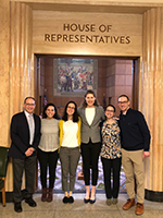 "A group of OHSU Pediatric Residents at the Oregon State House posing in a doorway above which reads ""House of Representatives."""