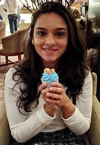 A woman smiling while sitting down holding a cupcake.