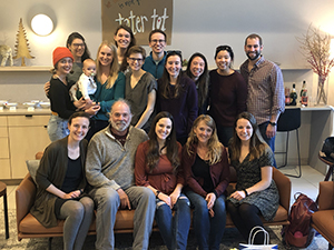A group of people pose smiling while at a baby shower.