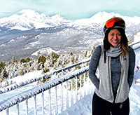 A woman at a ski resort standing with snowy mountains in the background.