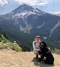 A woman crouching down posing next to her dog while on a hike with a mountain in the background.