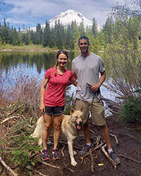 A woman, man and their dog smiling while on a walk with a river and mountain in the background.