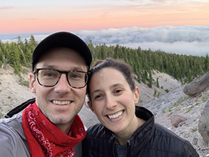 A man and a woman smiling taking a selfie while on a hike.