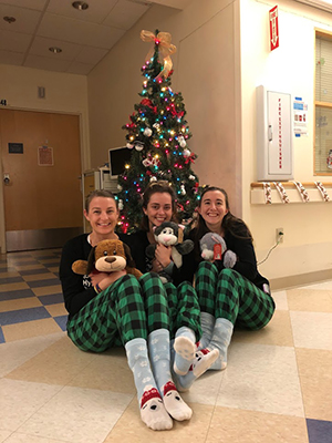 Three female pediatric residents sitting on the ground holding stuffed animals in front of a holiday tree at an OHSU clinic.
