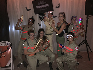 A group of people pose wearing Ghostbuster costumes.