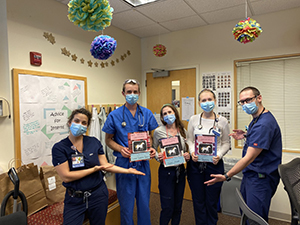 Five Pediatric Interns pose in clinic wearing PPE facemasks.