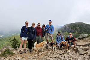 Four women, three men and three dogs in a line posing while on a hike on a cloudy day.