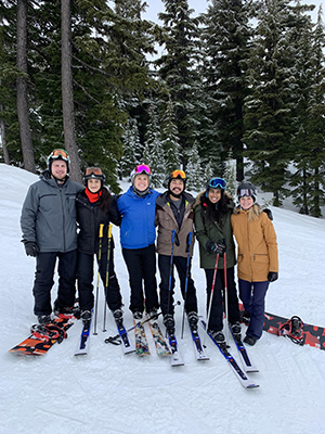 A group of people posing in a line while skiing and snowboarding on Mt. Hood.