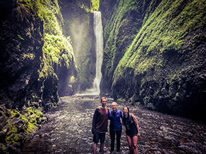 Two women and one man stand in a swimming hole with a waterfall behind them.
