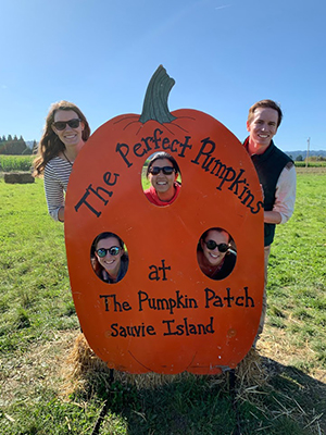 Four girls and one boy pose in a cut-out pumpkin at a pumpkin patch.