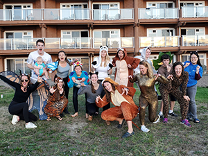 A group of OHSU Pediatric Residents pose outside a hotel wearing costumes.