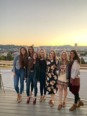 A group of women pose in a line on a rooftop bar at sunset with downtown Portland behind them.