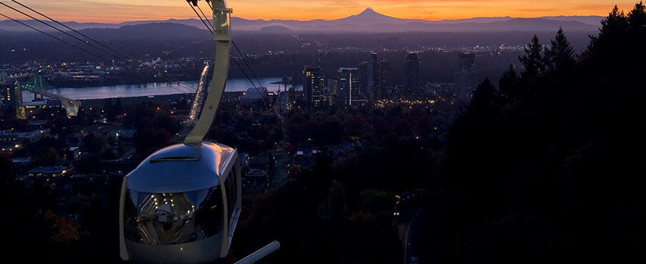 A scenic shot of the OHSU tram arriving at Marquam Hill at sunrise with Mt. Hood in the background.