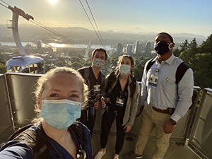 Four OHSU Pediatric Residents wearing PPE masks (two women and two men) standing at the OHSU Tram platform on a sunny morning.