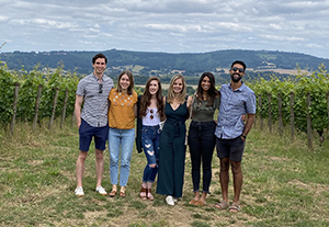 Four women and three men, all OHSU Pediatric Residents, pose while at a wine vinyard.