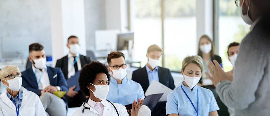 Medical students in classroom wearing masks with instructor's back in view.
