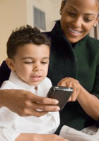 A mother and toddler look at mobile phone and smile
