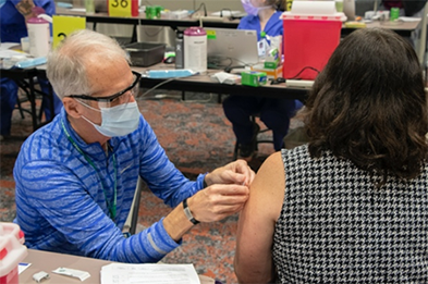 A person receives the COVID-19 vaccination at the Oregon Convention Center vaccine site