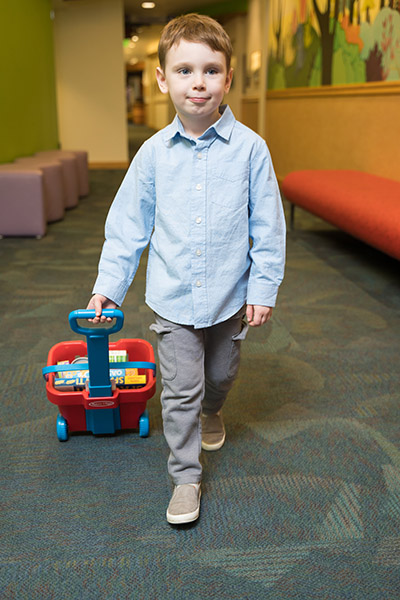 Photo of a boy walking and pulling a small wagon in a hallway at Doernbecher