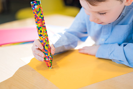 Photo of a child coloring on yellow paper with a large multicolor crayon