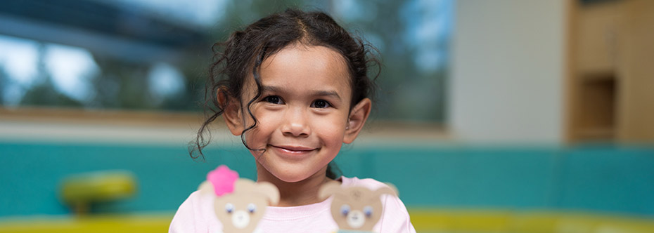 Photo of a girl smiling and holding paper teddy bears