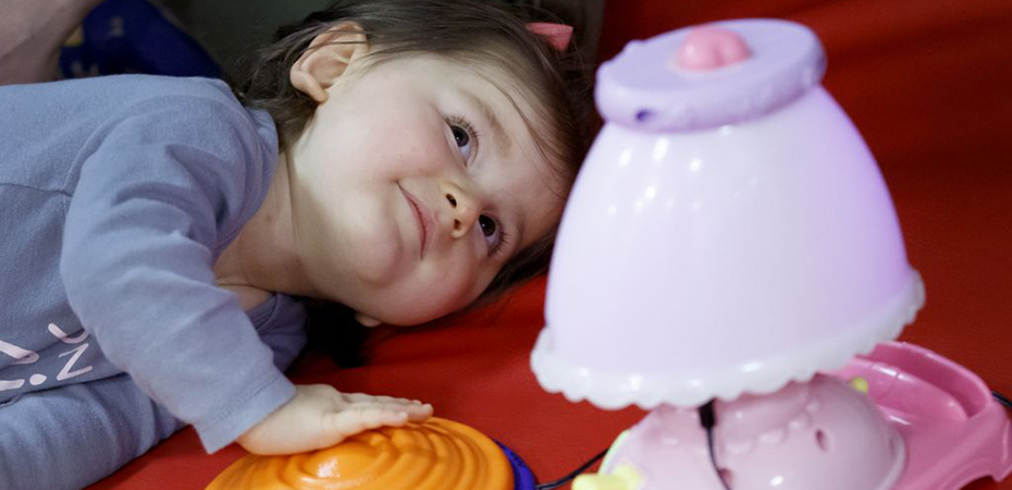 A little girl lying on her side pressing a button that is connected to assistive technology equipment.