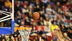 Stock photo of a basketball being thrown toward a hoop