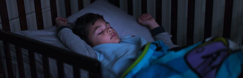 Stock photo of a child sleeping in a darkened room