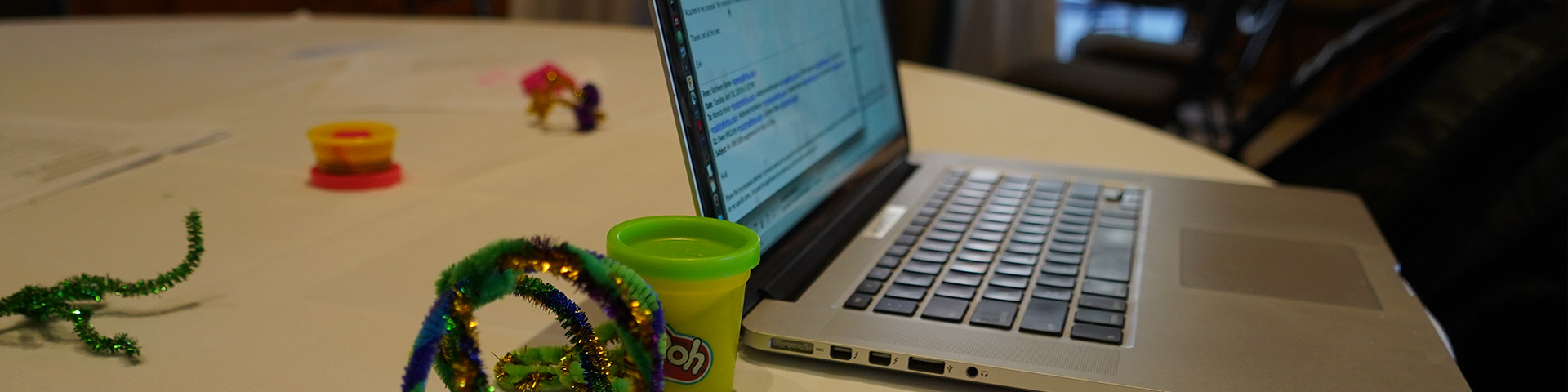 photo of a laptop screen on a table with pipe cleaners and play doh toys